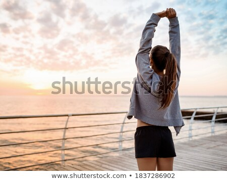 Brunette girl at the beach in sunrise. Stock photo © Massonforstock