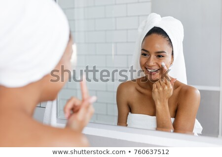 Stock photo: Attractive woman applying moisturiser