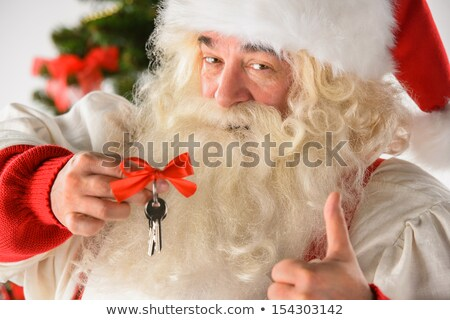 Santa Claus holding keys of new house or apartment and thumbs up Stock photo © HASLOO