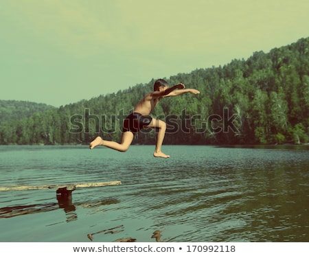 boy jumping in lake - vintage retro style Stock photo © Mikko