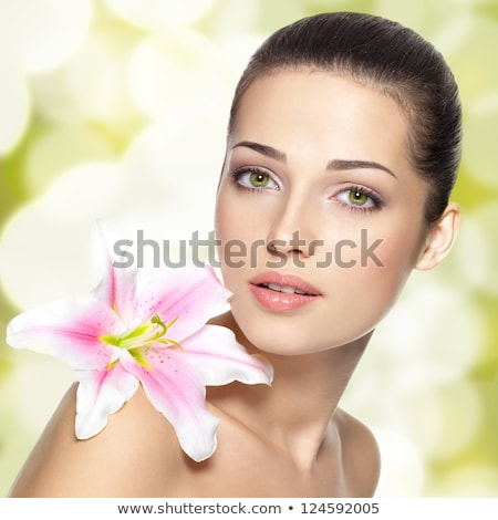 The face of a beautiful girl with a fresh flower lily Stock photo © HASLOO