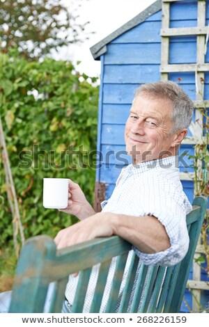 Zdjęcia stock: Senior Man Relaxing In Garden With Cup Of Coffee