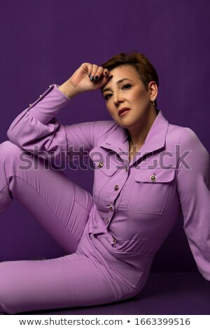 Fashion woman sitting, holding one hand to her forehead Stock photo © feedough