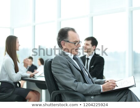 portrait of a pensive mature businessman in suit with his team working behind stock photo © deandrobot