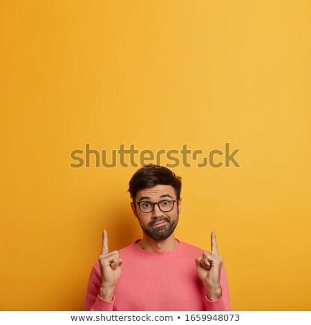 Perplexed man pointing upwards Stock photo © ozgur