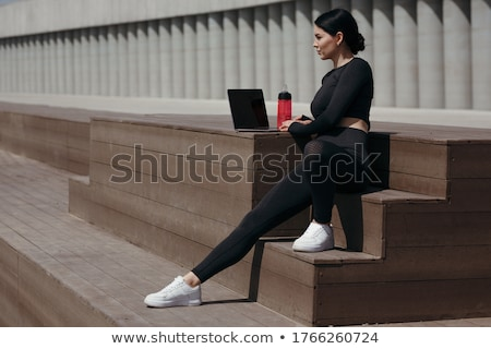 Young athletic girl sitting with laptop in tracksuit Stock photo © master1305