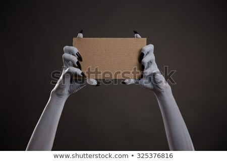 Creepy white hands with black nails holding blank cardboard  Stock photo © Elisanth