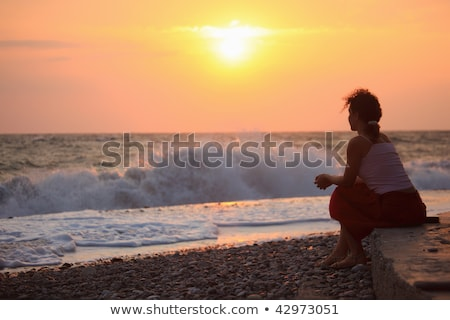silhouette sitting young woman on sunset wavy beach stock photo © paha_l