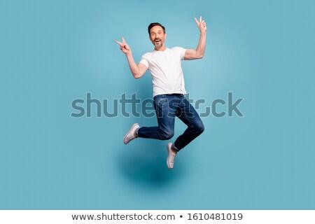 Szczęśliwy przystojny młody człowiek zwycięstwo gest Zdjęcia stock © deandrobot