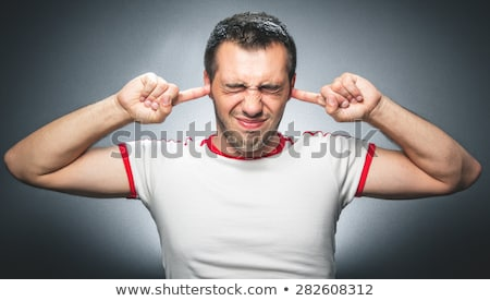 stressed young man close his ears and eyes on grey background Stock photo © Patramansky