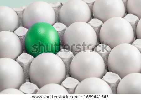 Egg box of white Easter eggs with one green one Stock photo © ozgur