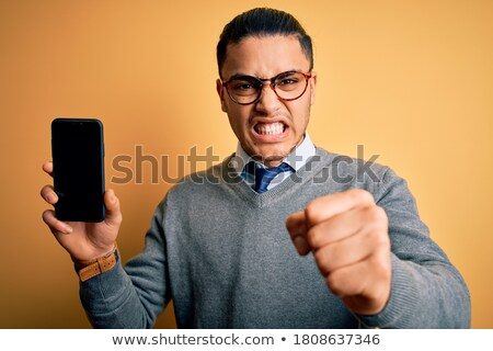 angry crazy young businessman holding smartphone and shouting stock photo © deandrobot