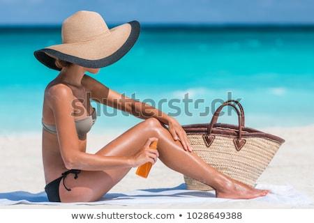 woman spraying sunscreen oil to her skin on beach Stock photo © dolgachov