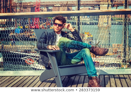 young man in leather jacket sitting on chair and thinks Stock photo © feedough