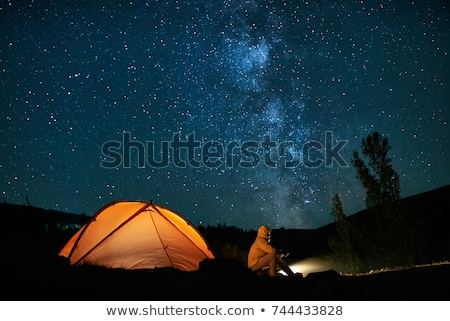 Milky Way, yellow glowing tent and mountains Stock photo © denbelitsky