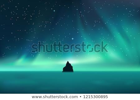 dark rock against northern lights landscape with stars stock photo © marysan