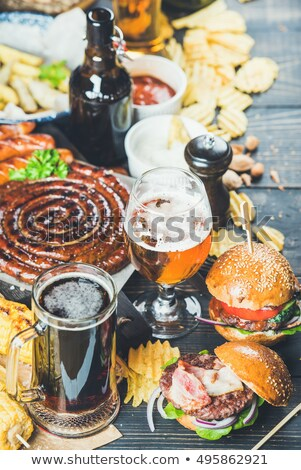 fresh beef burger with sauce and vegetables and glass of lager craft beer with potato chips fries on stock photo © denismart