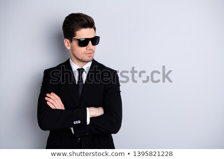 portrait of handsome smart man wearing sunglasses and black tuxe stock photo © feedough