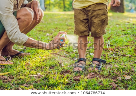 Foto d'archivio: Dad And Son Use Mosquito Sprayspraying Insect Repellent On Skin Outdoor