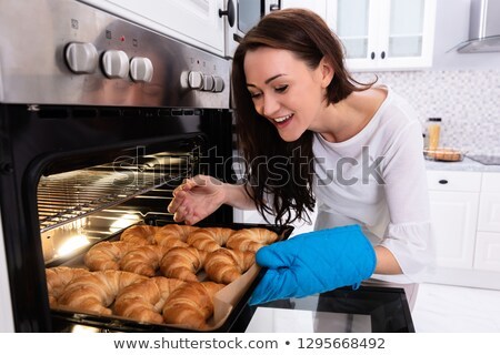 Woman Checking Baked Croissants In Oven Stock photo © AndreyPopov