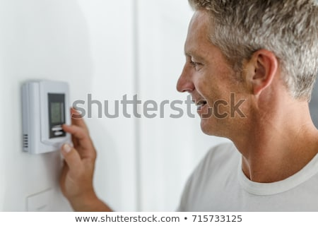 Smiling Man Adjusting Thermostat On Home Heating System Stock photo © Lopolo