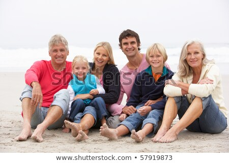 Portrait Of A Family Sitting On Sand At Beach Stock photo © AndreyPopov