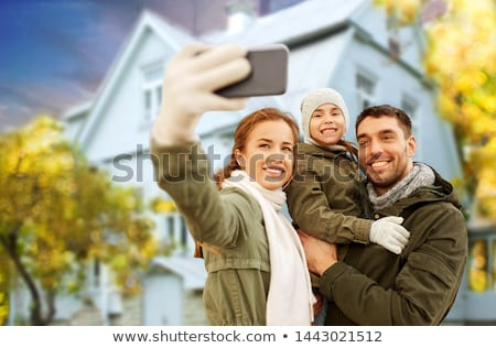 family photographing by smartphone on autumn beach stock photo © dolgachov
