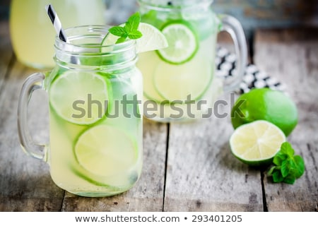 glass of mojito with lime and mint ice cube close-up on dark wood background Stock photo © galitskaya