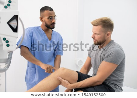 young doctor in uniform consulting sportsman while pointing at his sick leg stock photo © pressmaster