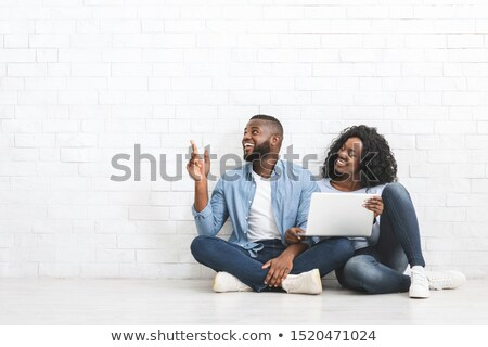 Relaxed young African American woman sits on floor in empty room near sofa with pedigree dog, enjoys Stock photo © vkstudio
