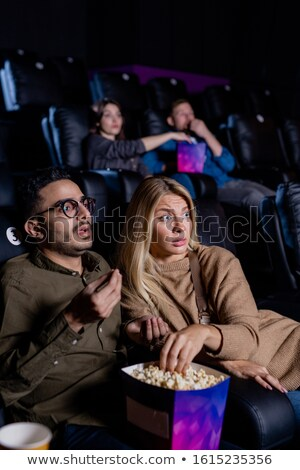 Tense young couple with box of popcorn watching action movie at leisure Stock photo © pressmaster