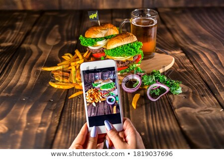 Woman making a photo with a smartphone of assortment of home made sandwiches with various toppings Stock photo © dash