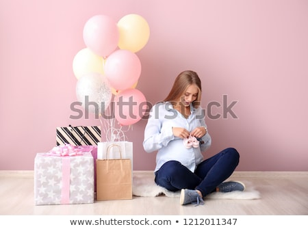 beautiful pregnant woman with baby shoes on belly stock photo © lunamarina