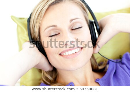 Radiant woman is listening the music with headphones  Stock photo © wavebreak_media