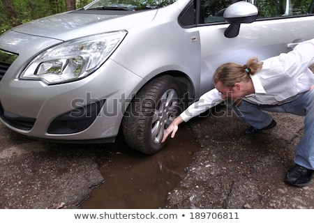 Upset driver man in front of automobile watching damaged car of  Stock photo © vladacanon