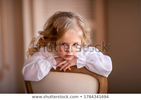 Little girl in a colored dress on a chair in the studio and shy Stock photo © RuslanOmega
