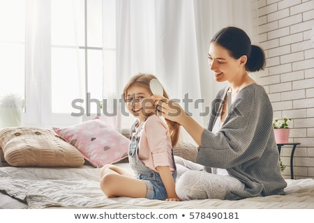 Mother combing her daughters hair Stock photo © IS2