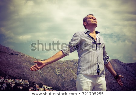 Man outdoors with arms raised Stock photo © IS2