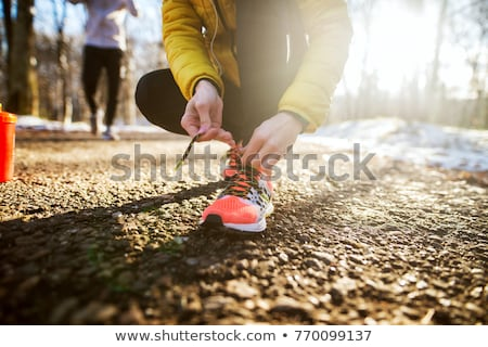 Close up of fitness girl tying her shoelaces Stock photo © deandrobot
