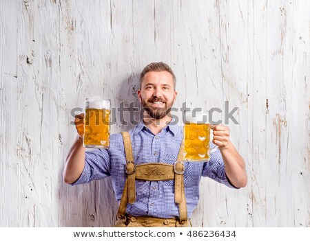 Two cheerful German man drink beer out wooden mug Stock photo © orensila