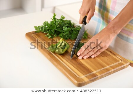 juicy slices of yellow pepper cut a womans hands into a wooden board on a white kitchen table with stock photo © artjazz
