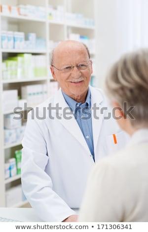 Pharmacist servicing senior customer in her pharmacy Stock photo © Kzenon