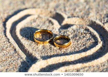 Golden Wedding Rings Inside The Heart Shape On Sand Stock photo © AndreyPopov