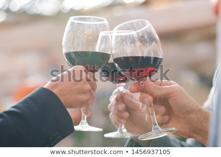 Hands of friends or business partners clinking with wineglasses with red wine Stock photo © pressmaster