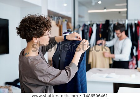 Young professional clothes designer working over unfinished dress on dummy Stock photo © pressmaster