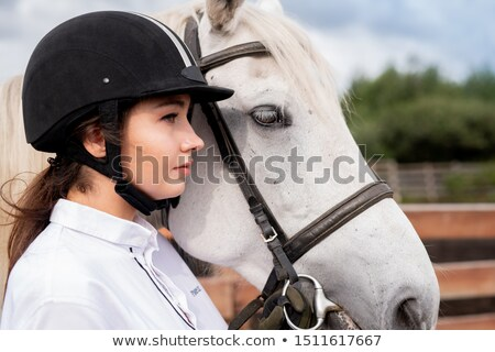 Young calm female in white shirt and equestrian helmet standing by racehorse Stock photo © pressmaster