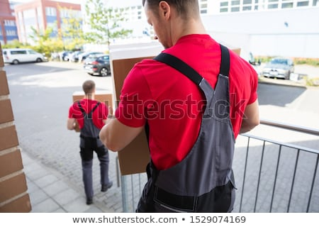 Stock photo: Male Young Movers Walking With Cardboard Boxes On Street