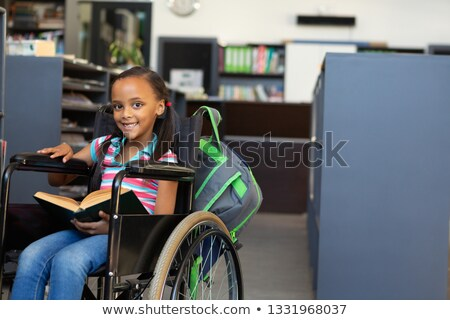 Front view of a happy disabled mixed-race schoolgirl reading a book in the classroom at school Stock photo © wavebreak_media