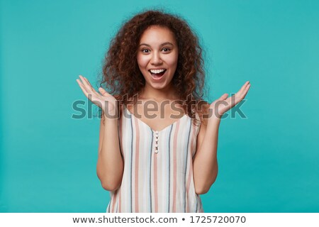 Studio shot of joyful excited woman dressed in striped shirt, spreads hands near face, wears optical Stock photo © vkstudio