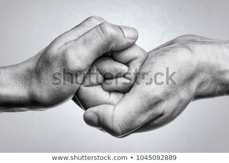 two hands holding each other on black background stock photo © andreykr